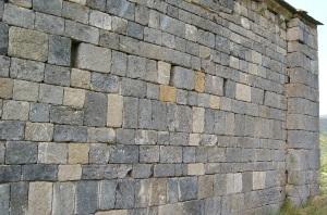 Muro con paramento de piedra vista y vanos pequeños.